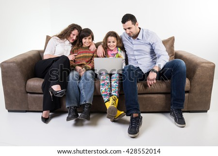 Family at home sitting at sofa - stock photo