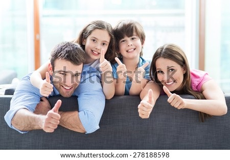Family at home with thumbs up  - stock photo