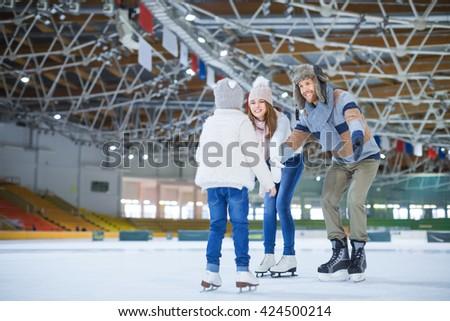 Family at ice-skating rink - stock photo