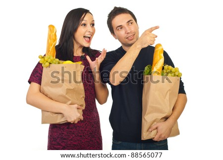Family at shopping groceries,man pointing away to his amazed wife isolated on white background - stock photo