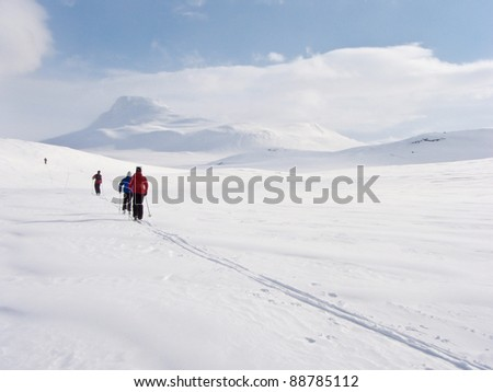 Family at ski in a row in flat terrain heading towards a mountain summit in the norwegian mountains at easter - stock photo