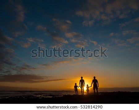 Family at sunset by the ocean. People hold hands and look at the setting sun. We see people from the back.