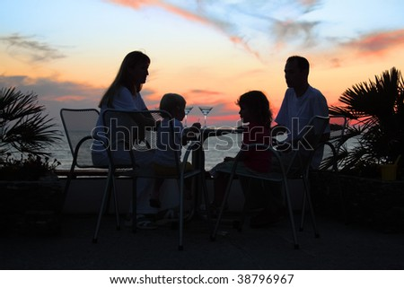 family at table on beach on sunset - stock photo