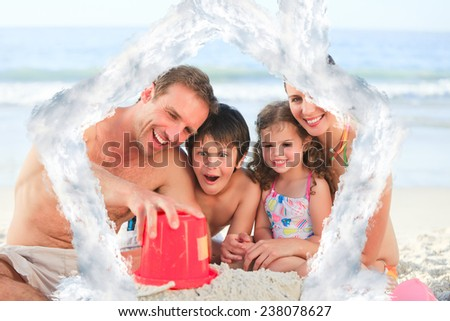 Family at the beach against house outline in clouds