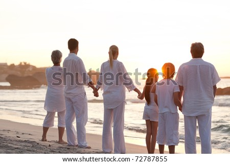 Family at the beach during the sunset - stock photo