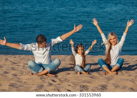 Family at the beach. lotus posture  hands up, happiness  jeans - stock photo
