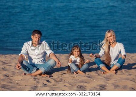 Family at the beach. lotus posture. jeans - stock photo