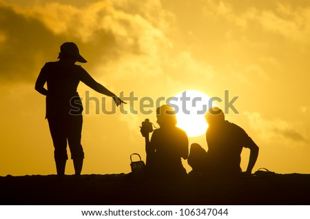 family at the beach with a beautiful sun on an orange sky at the background