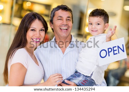Family at the mall holding an open sign - stock photo
