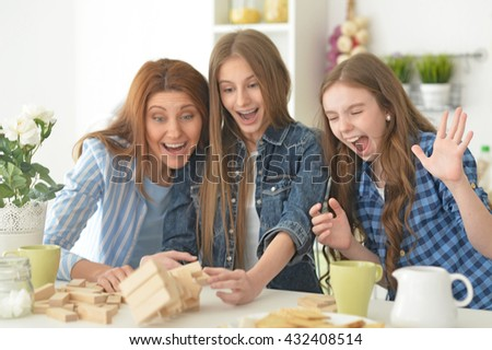 Family at the table playing board game - stock photo