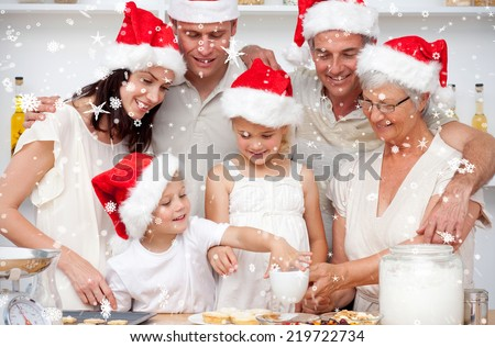 Family baking Christmas cakes and sweets in the kitchen against snow falling - stock photo