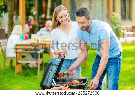 Family barbeque. Happy young couple barbecuing meat on the grill while other members of family sitting at the dining table in the background  - stock photo