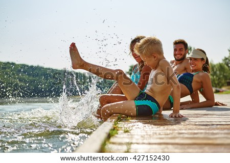 Family bathing and splashing water with their foot at a lake in summer - stock photo