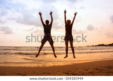 family beach holidays, happy young couple jumping at sunset