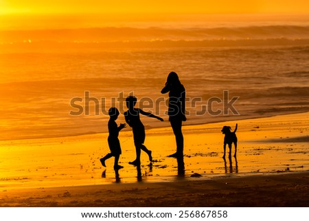 Family beach walk at sunset - stock photo
