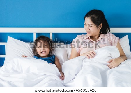 Family Bed : Mother and daughter play in bed / blue wall