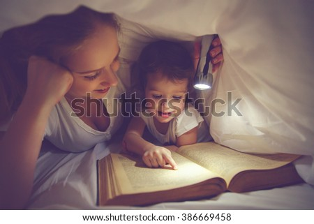Family bedtime. Mom and child daughter reading a book with a flashlight under the blanket in bed - stock photo