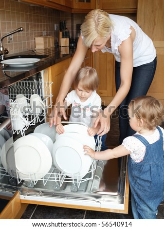 Family besides open dishwasher in the kitchen - stock photo