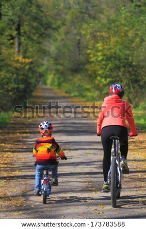 Family bike ride in autumn forest - stock photo