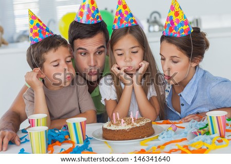 Family blowing candles together while celebrating a birthday party - stock photo
