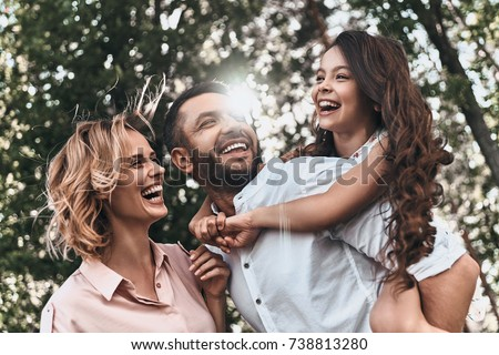 Family bonds. Happy young family of three smiling while spending free time outdoors