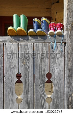Family boots on the balcony fence in mountain village in Slovakia - stock photo