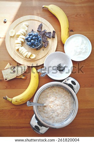 Family breakfast table: oatmeal porridge with bananas, blueberries and dark chocolate, empty bowls, tea spoons, bread and yogurt on wooden table, high angle view - stock photo