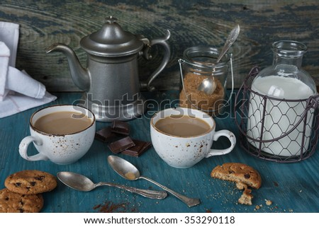 Family breakfast - two cups of coffee with milk and homemade oatmeal cookies with chocolate on a blue wooden vintage table, rustic style, low key