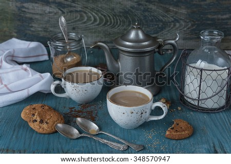 Family breakfast - two cups of coffee with milk espresso and homemade oatmeal cookies with chocolate on a blue wooden vintage table, rustic style, low key