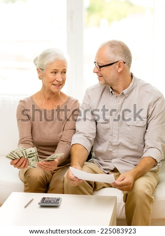 family, business, savings, age and people concept - smiling senior couple with papers, money and calculator at home