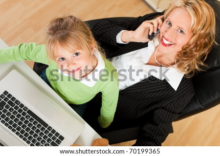 Family Business - telecommuter Businesswoman and mother with kid on her lap is making a phone call, both are looking to the viewer - stock photo