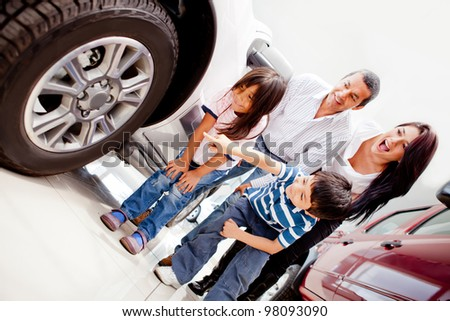 Family buying a car and pointing at the wheels - stock photo