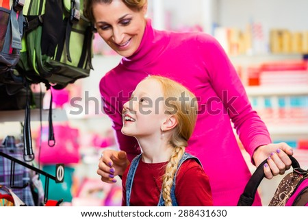 Family buying school satchel or bag in store preparing for first day in school - stock photo