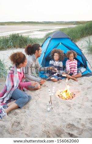 Family Camping On Beach And Toasting Marshmallows - stock photo
