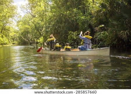 Family canoe ride down a beautiful tropical river - stock photo