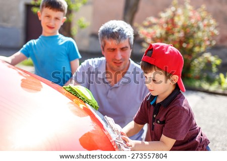 Family car wash, men at work. Little boy in cap cleaning the headlight - stock photo