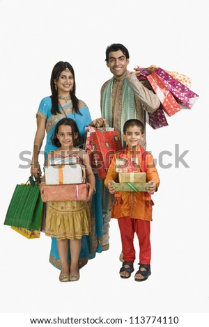 Family carrying shopping bags and gifts for Diwali - stock photo