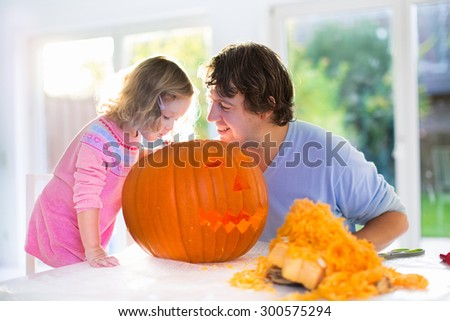 Family carving pumpkin at Halloween. Parents and children decorate the house. Kids and parents trick or treat. Father and child carve squash at home. Toddler kid with jack-o-lantern.  - stock photo