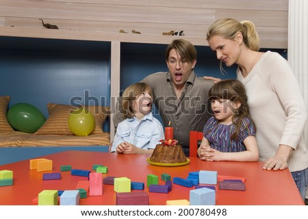 Family celebrating birthday father blowing candle on cake - stock photo