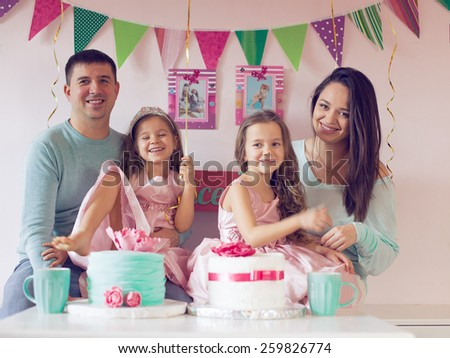 Family celebrating birthday princess party of two 6 years old children - stock photo