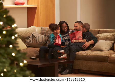 Family Celebrating Christmas At Home Viewed From Outside - stock photo
