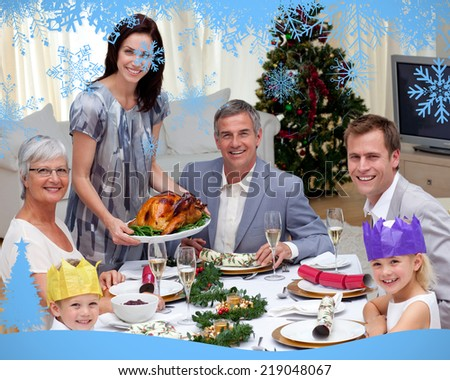 Family celebrating Christmas dinner with turkey against snow flake frame in blue