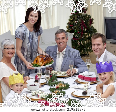 Family celebrating Christmas dinner with turkey against snowflake frame - stock photo
