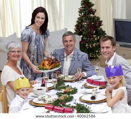 Family celebrating Christmas dinner with turkey at home - stock photo