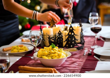 Family celebrating Christmas eve with traditional dinner Wiener sausages and potato salad, mom is filling the plates - stock photo