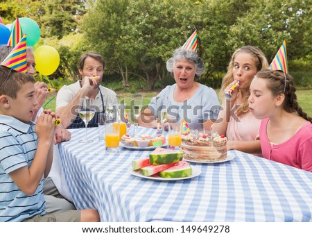 Family celebrating little girls birthday outside at picnic table blowing party horns - stock photo