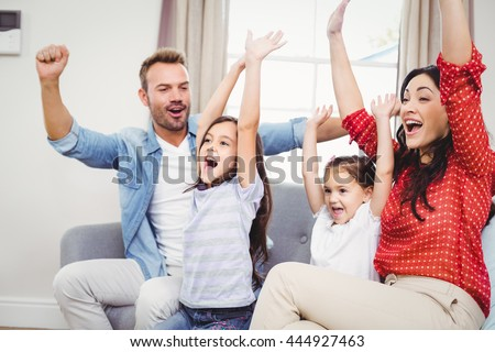 Family cheering while sitting on sofa at home