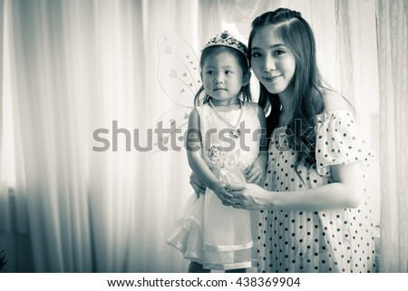 family, child and home concept - smiling parents and little girl  at home.Backlit shot ,Picture is black and white - stock photo