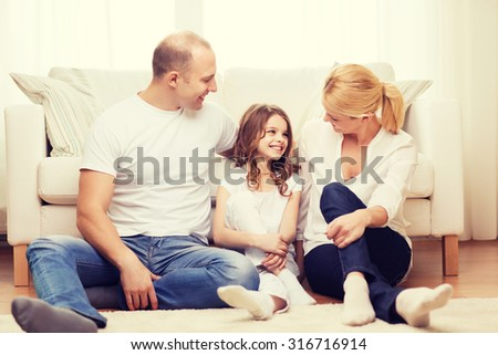 family, child and home concept - smiling parents and little girl sitting on floor at home - stock photo