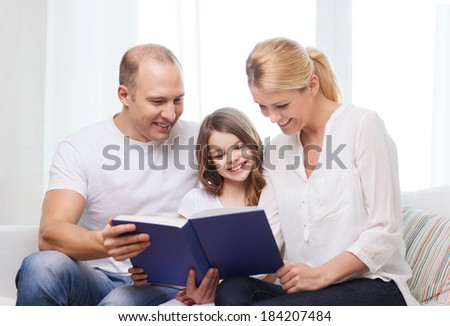 family, child and home concept - smiling parents and little girl with book at home - stock photo